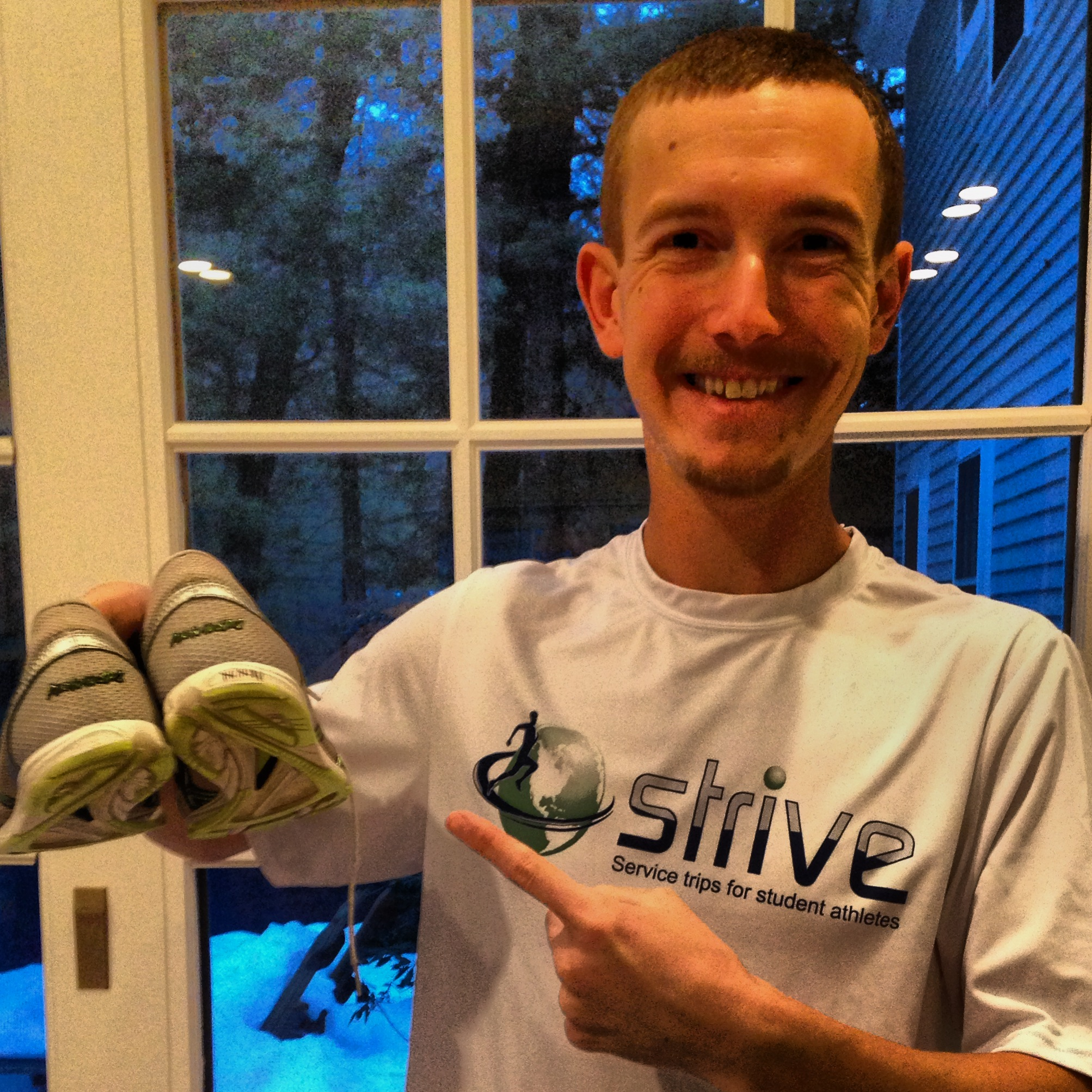 Ty happily poses with the shoes that have never lost a race and now have a world record!